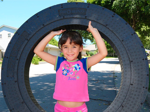Little girl in pink shirt holding big PRO-RING